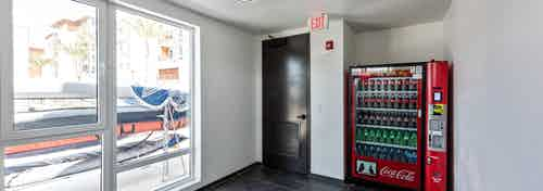Interior of boat house vending machine room facing AMLI Marina Del Rey apartment building and paddleboards through window