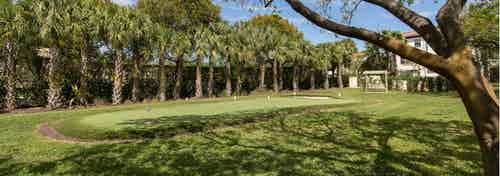 AMLI Toscana Place outdoor putting green lined with palm trees and replicated greens to putt