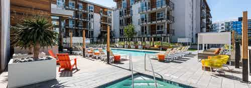 Daytime view of AMLI Marina Del Rey swimming pool area with varied style lounge seating, cabanas daybeds and lush landscaping