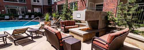 Exterior view of the outdoor fireplace at AMLI Park Avenue apartments with multiple seating areas and a view of the pool