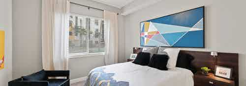 Interior view of an AMLI 8800 apartment bedroom with a bed underneath blue geometric wall art and a window view