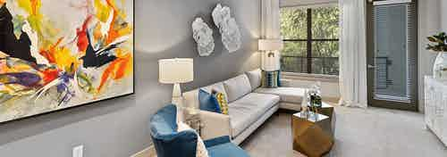 Interior of AMLI Parkside apartment living room with white sectional sofa and blue armchair in front of window and patio door
