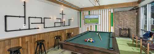 Clubroom at AMLI Decatur with billiards table set with balls and cue with a large screen TV and barstools on green carpet