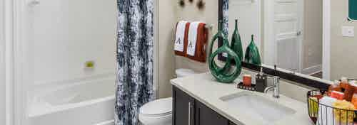 Bathroom at AMLI Buckhead with dark wood vanity sink and a white bathtub with a dark grey and white patterned curtain
