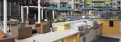 Poolside barbeque grills at AMLI Riverfront Green apartments with a cabana area with various comfortable chairs and tables
