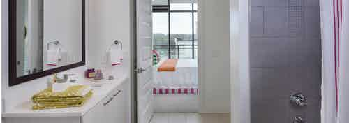 Bathroom at AMLI 3464 with white vanity sink and a grey tiled shower with an open door peaking into the connected bedroom