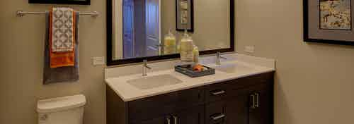 Interior view of AMLI Deerfield bathroom with double vanity sinks and white countertops with dark espresso wood cabinets