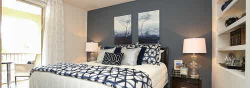 Interior view of AMLI Warner Center apartment bedroom with blue accent wall, night stands with lamps and access to patio