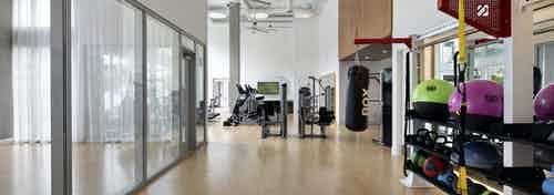 AMLI Park Broadway apartments fitness center with punching bag and TRX system and colorful exercise and medicine ball rack
