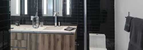 Interior view of AMLI Midtown Miami apartment bathroom black subway tile walls and modern zebra wood vanity and toilet