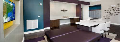 AMLI Buckhead mailroom with dark wood floors and a white table and chairs with teal and plum accent walls and a large TV