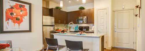 A kitchen at AMLI Interlocken apartments and bar chairs at granite counter top and view of large artwork and the front door