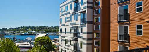 Sunny daytime exterior view from an apartment at AMLI Mark24 facing Market Street that overlooks Salmon Bay and docked boats
