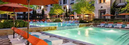 Pool at AMLI on Riverside at night with orange umbrellas, white lounge chairs and vibrant trees surrounding the water