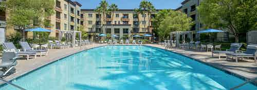 Daytime view of large pool at AMLI Warner Center apartments with blue cushioned lounge chairs and cabanas and umbrellas