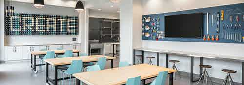 Maker space at AMLI Addison with tables and barstool seating with a variety of tools to create with hanging on the wall