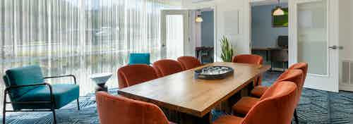 AMLI South Shore co working space with orange office chairs around wooden table with blue carpet and floor to ceiling windows