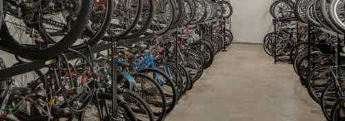 Interior view of roughly fifty resident bicycles in a well lit storage area with cement flooring and white walls at AMLI 900
