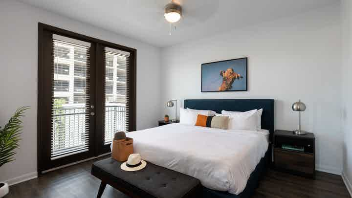Interior of AMLI 300 apartment bedroom with private balcony and large windows with shades and a ceiling fan