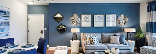 Interior of AMLI Spanish HIlls apartment living room with blue accent wall and peek into dining area with fully set table