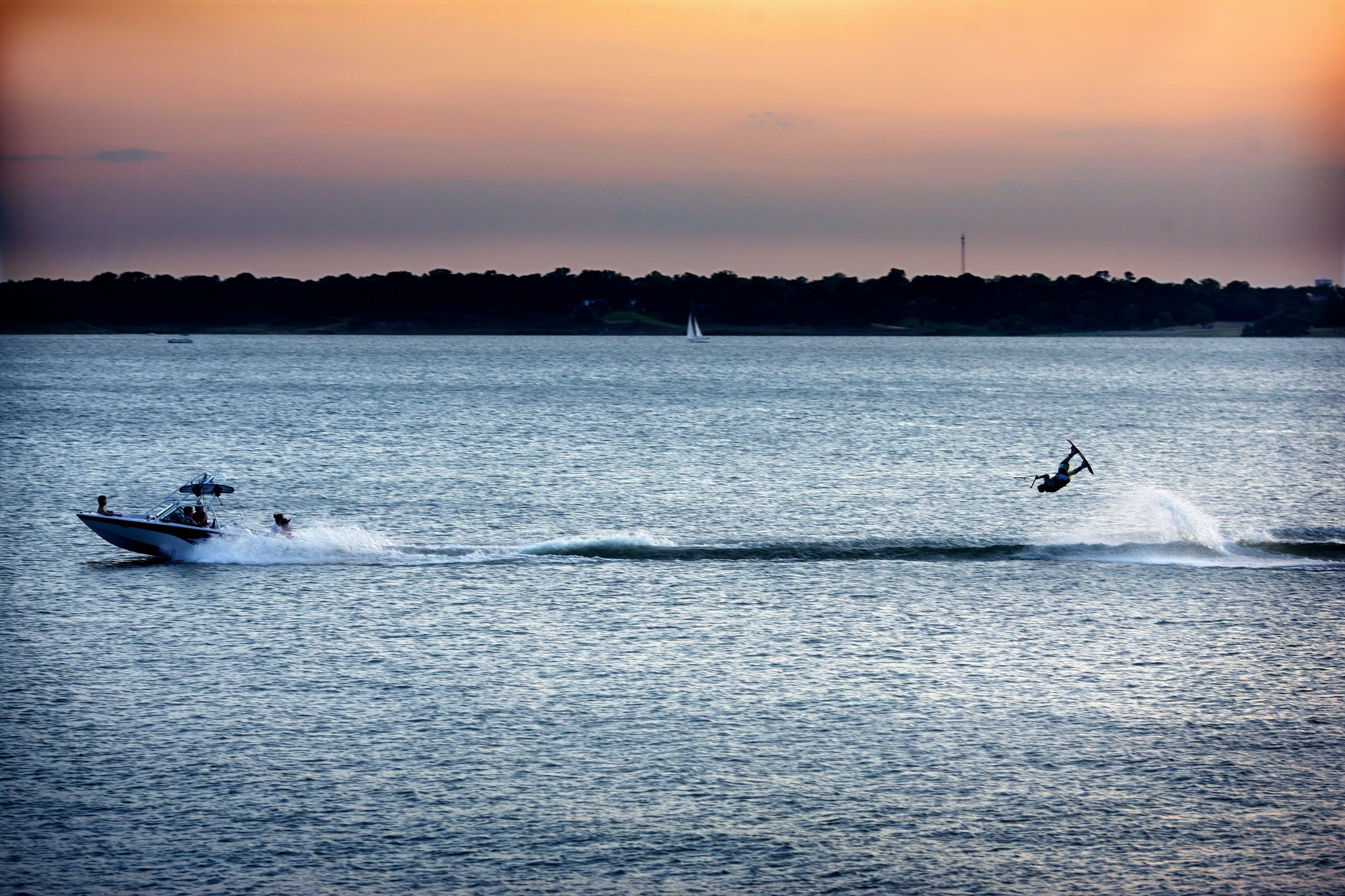 A lake at sunset with a boat racing across the water pulling a man on a wakeboard