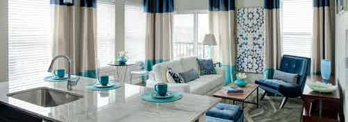 Interior view of connecting living room with blue and white decor from the kitchen at AMLI Evanston apartment community