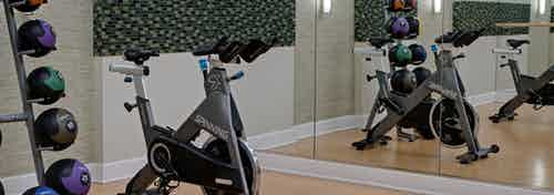 Close up view of fitness center at AMLI Evanston with exercise bike and shelved weights in front of a large wall mirror