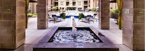 Exterior daytime view of AMLI RidgeGate centered fountain with connecting water channel to pool with blue tile trim surround