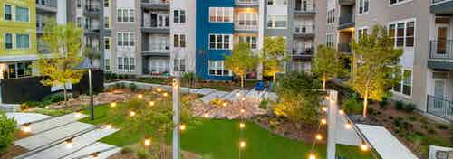 AMLI Piedmont Heights courtyard in the middle of the buildings containing grass and hanging lights and lined with small trees