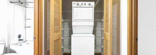 Interior view of updated AMLI 535 apartment stacked white washer and dryer with slight view of upgraded bathroom