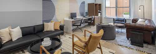 Business center at AMLI Downtown apartments with two computer stations and printer and 2 leather seating areas on area rugs
