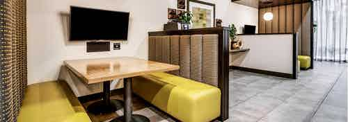 A cyber cafe at AMLI Cherry Creek apartments with padded booth seating and table and television and gray floor and wall art