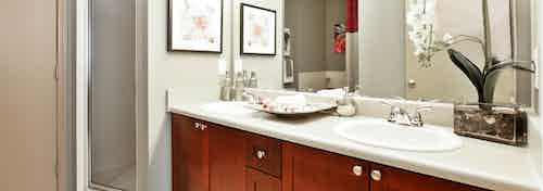 Interior of AMLI Lindbergh bathroom with a single dark wood vanity sink with a white countertop and a standup shower