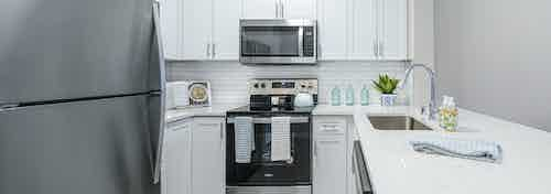 AMLI Bellevue Park apartment kitchen with stainless steel appliances and white cabinets and countertop and tiled backsplash