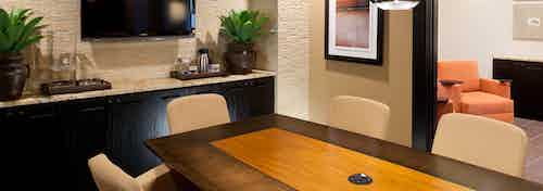 Interior view of conference room at AMLI at Escena apartment building with wood table and chairs and big screen TV