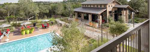 Exterior view of pool at AMLI Covered Bridge with colorful poolside dining seating and an accessibility pool lift