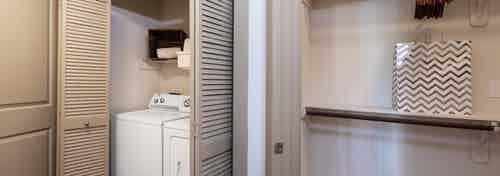 Interior view of two white laundry machines tucked in a closet with folding doors at AMLI Eastside apartment community