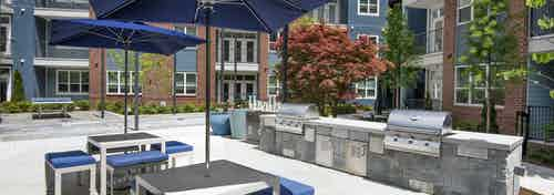 Daytime view of AMLI Decatur poolside grill area with two stainless grills and two tables with blue umbrellas and chairs