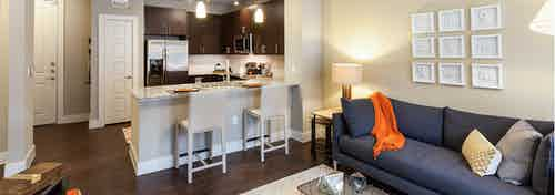 Interior of living room and kitchen at AMLI West Plano with a dark grey couch and tan barstools at a granite counter