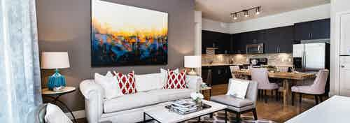 Interior of AMLI RidgeGate furnished living room with white sofa facing dining area and kitchen with mosaic tile backsplash