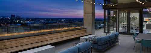 Nighttime view from AMLI Arts Center rooftop with blue outdoor couches overlooking the city with string lights hanging above