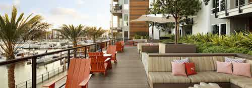 Daytime view of AMLI Marina Del Rey apartment elevated outdoor lounge with cozy seating overlooking the marina and palm trees
