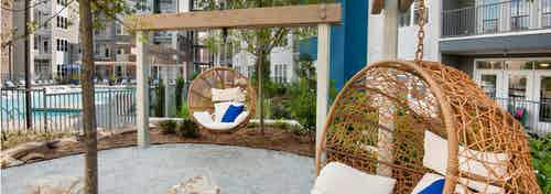 AMLI Piedmont Heights sitting area in courtyard near the pool showing wicker egg shaped swinging chairs with cream cushions