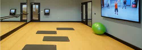 AMLI Deerfield yoga and pilates studio with fitness classes on demand on large screen including yoga mats and balls and barre