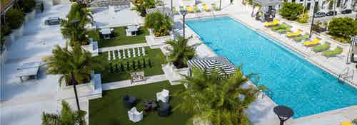 Exterior Rooftop view of the AMLI Dadeland Pool with black and white striped cabanas life size chess game and pool furniture