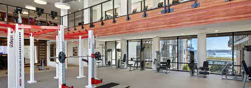 Interior of AMLI Marina Del Rey apartment fitness center with strength workout equipment and motion cage facing the marina