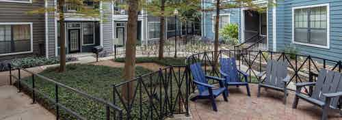 AMLI Eastside courtyard with tall trees and green landscape with black railings and gray and blue chairs set on brick pavers