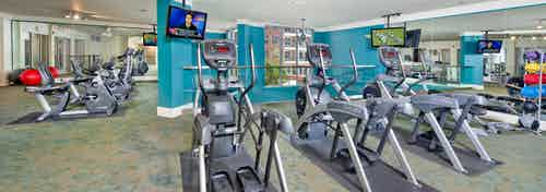 Fitness center at AMLI North Point with blue walls and flat screen TVs above exercise equipment including elliptical machines