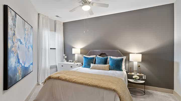 AMLI Parkside apartment bedroom with bed centered on gray wall and nightstands with lamps and a window with white curtains