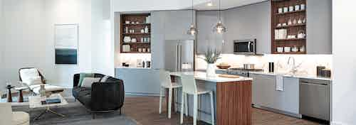 Interior view of AMLI Fountain Place European style kitchen with island and stainless steel appliances with light wood floors